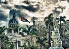与国会大厦大厦和古巴人旗子的哈瓦那中央公园雕象 库存图片