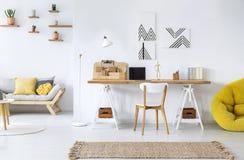 与图表、书桌、沙发和黄色蒲团的现代家庭办公室内部 免版税库存照片