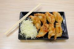 与圆白菜服务的自创gyoza在有筷子的黑色的盘子 免版税库存图片