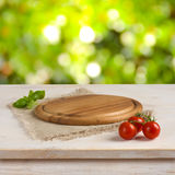 与圆的委员会的厨房用桌在绿色bokeh背景 免版税图库摄影