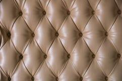 与圆的按钮的米黄皮革详细的背景 免版税图库摄影