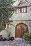 与圆的木门的独特的美好的家庭上升在房子墙壁上的入口和藤 免版税库存照片