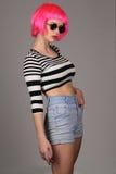 与圈子太阳镜和桃红色假发的模型 关闭 灰色背景 免版税库存图片
