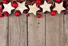 与土气木星装饰品和中看不中用的物品的圣诞节顶面边界在年迈的木头 库存照片