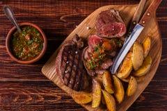与土豆楔子、辣调味汁和香料的烤牛排 库存图片
