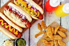 与土豆楔子的热狗,在土气白色木头的场面上 免版税库存照片