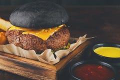 与土豆楔子的黑小圆面包汉堡关闭  免版税库存图片