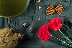 与圣乔治丝带和两支康乃馨的5月9日,在军用衣裳背景  图库摄影