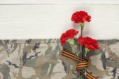 与圣乔治丝带的红色康乃馨在卡其色的背景 库存图片