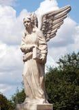 与圣经书的一个天使在教会附近的庭院里 免版税库存图片