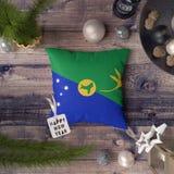 与圣诞岛旗子的新年快乐标记在枕头 在木桌上的圣诞装饰概念与可爱的对象 免版税库存图片