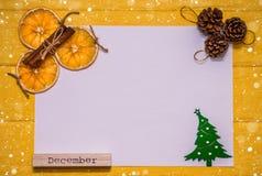 与圣诞树、桂香、橙色切片、爆沸和词` 12月`的白色白纸在明亮的黄色背景 图库摄影