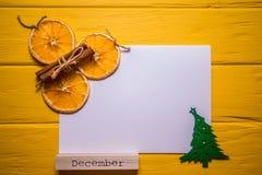 与圣诞树、桂香、橙色切片和词` 12月`的白色白纸在明亮的黄色背景 美好的n 免版税库存图片