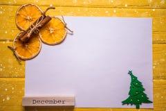 与圣诞树、桂香、橙色切片和词` 12月`的白色白纸在明亮的黄色背景 免版税库存图片
