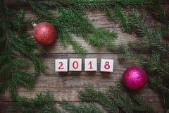 与圣诞树的图片分支,与第的块2018年并且戏弄红色球 免版税库存图片