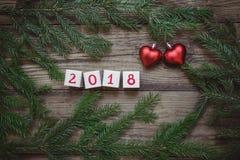 与圣诞树的图片分支,与第2018年和两红色心脏的块 免版税库存图片