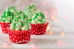 与圣诞树的圣诞节杯形蛋糕塑造,闪烁发光物和光 库存照片