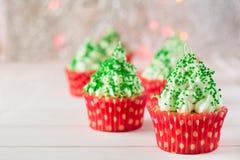 与圣诞树的圣诞节杯形蛋糕塑造,闪烁发光物和光 免版税库存图片