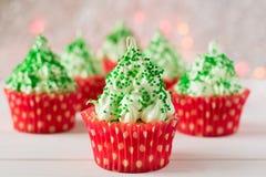与圣诞树的圣诞节杯形蛋糕塑造,闪烁发光物和光 库存图片