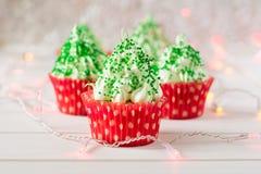 与圣诞树的圣诞节杯形蛋糕塑造,闪烁发光物和光 免版税图库摄影
