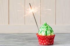 与圣诞树的圣诞节杯形蛋糕塑造,闪烁发光物和光 免版税库存照片
