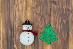 与圣诞树的手工制造雪人在木背景 免版税库存图片