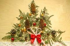 与圣诞树的明亮的胶合板,与冷杉球果的枝杈在鞋带丝带的金钟柏和巧克力 免版税图库摄影