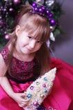 与圣诞树的逗人喜爱的孩子 图库摄影