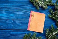 与圣诞树branche和笔记本的新年装饰做的在蓝色木背景上面veiw嘲笑的名单  免版税图库摄影