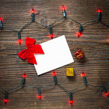 与圣诞灯的空的明信片在木桌上 免版税图库摄影
