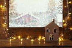 与圣诞灯的窗口基石在冬天背景前面 库存照片