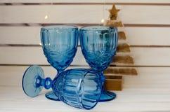 与圣诞灯的蓝色葡萄酒玻璃 库存图片