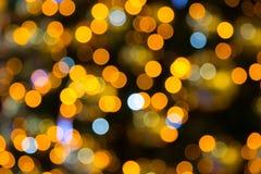 与圣诞灯的黄色,黑暗和红色背景boken 免版税库存图片