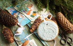 与圣诞老人、云杉的锥体、分支和明信片的图片的姜饼在木背景 圣诞节装饰隔离白色 库存图片