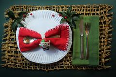 与圣诞老人套餐巾用的小环的蝶形领结餐巾在有绿色餐巾和霍莉的一块手工制造板材 图库摄影