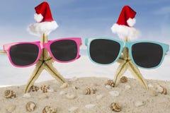与圣诞老人帽子和太阳镜的两个海星 图库摄影