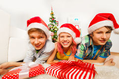 与圣诞老人帽子和微笑的愉快的青少年的孩子 库存图片