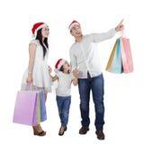 与圣诞老人帽子和购物袋的家庭 免版税库存照片