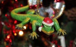 与圣诞老人帽子圣诞节装饰品的壁虎与与光的被弄脏的树在背景-选择聚焦中 免版税库存图片