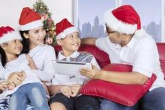 与圣诞老人帽子用途片剂的家庭在沙发 库存照片