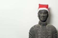 与圣诞老人帽子的中国赤土陶器战士雕象 免版税库存照片