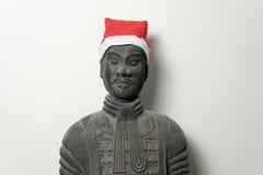 与圣诞老人帽子的中国赤土陶器战士雕象 库存照片