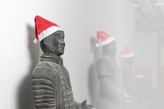 与圣诞老人帽子的中国赤土陶器战士雕象 免版税图库摄影