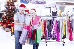 与圣诞老人帽子的亚洲家庭在商店 库存照片