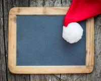 与圣诞老人帽子的圣诞卡空白 免版税库存图片