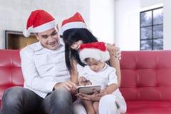与圣诞老人帽子的家庭使用在沙发的片剂 免版税库存照片