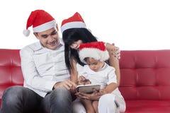 与圣诞老人帽子的家庭使用片剂 免版税库存图片