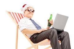 与圣诞老人帽子的成熟商人在椅子,饮用的啤酒和 免版税图库摄影