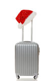 与圣诞老人帽子的旅行手提箱在把柄 免版税库存照片
