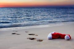 与圣诞老人帽子的日落在海滩 库存图片